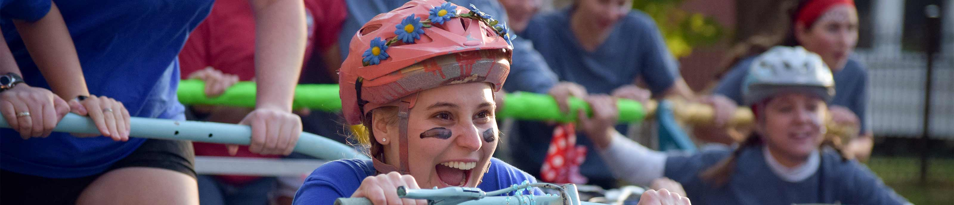 Student having fun riding in a bed at bed races