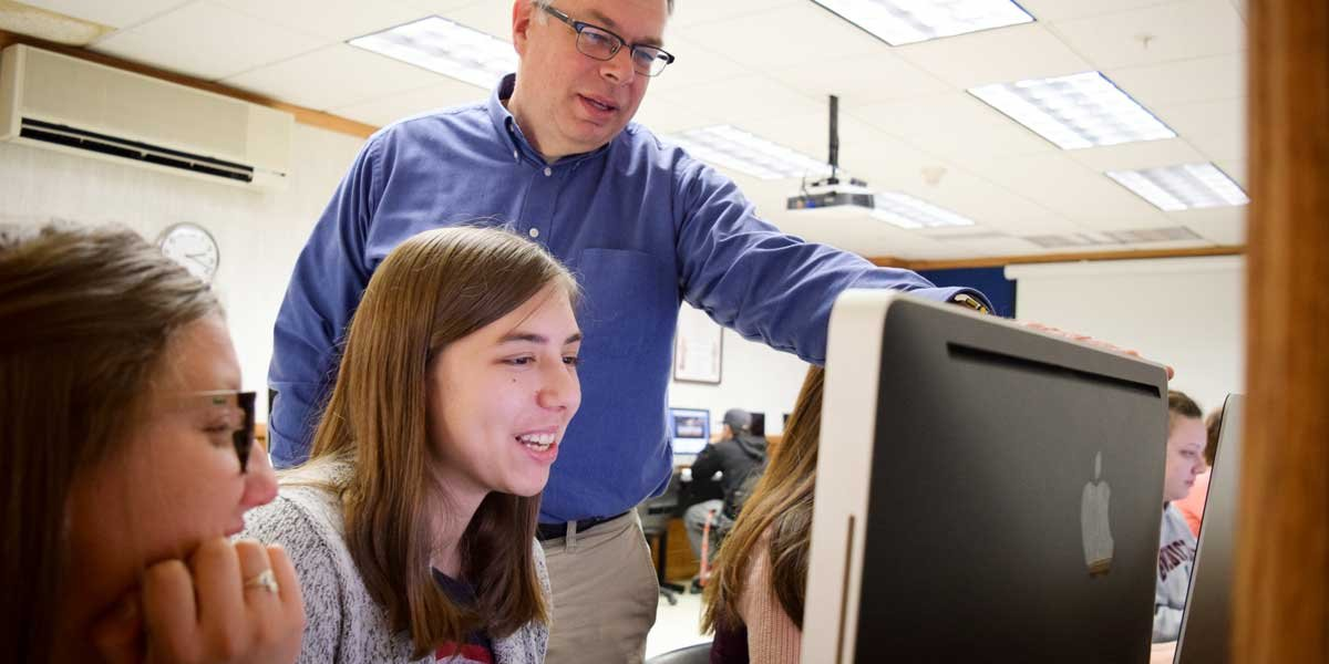 Professor Kevin Page works with students at a computer workstation