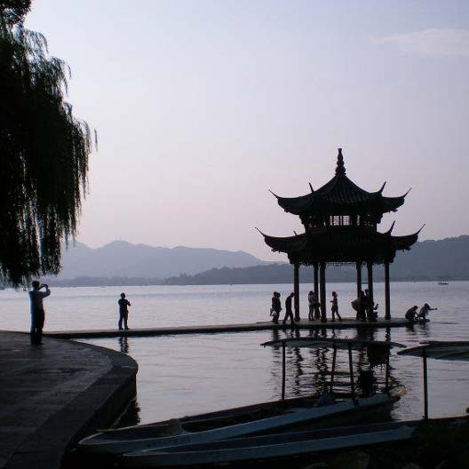 An evening photo of a lake with a gazebo