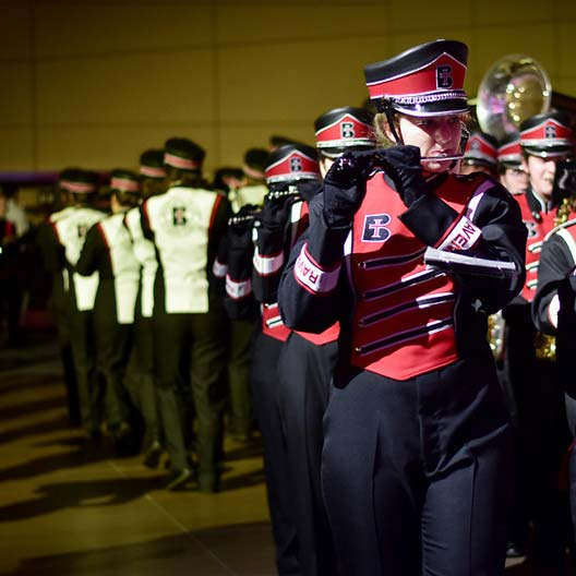Raven Regiment flutist marching with band in the background