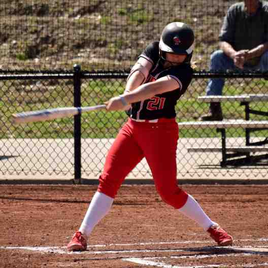 Softball player swinging at a pitch