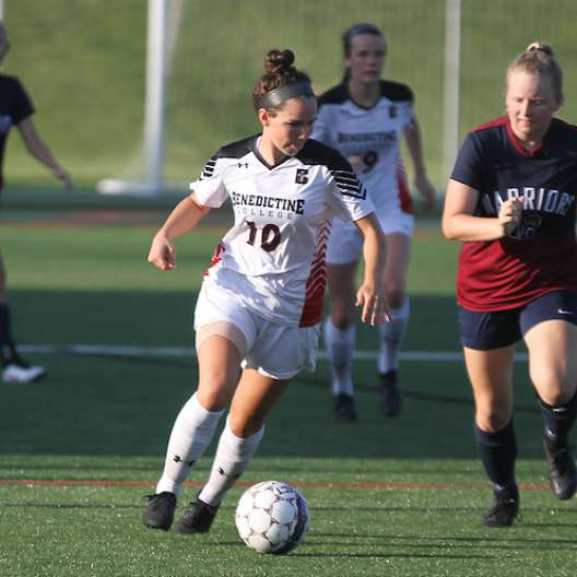 Benedictine College Women's Soccer player pushing the ball down the field