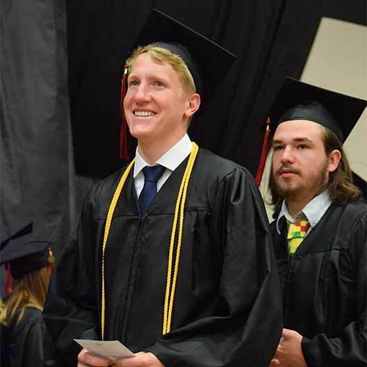 Graduating student smiling on his way to receive his diploma
