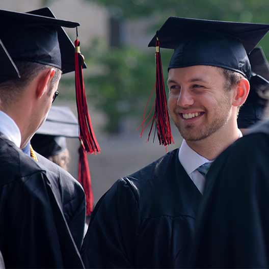 Graduate smiling with friends while in cap and gown