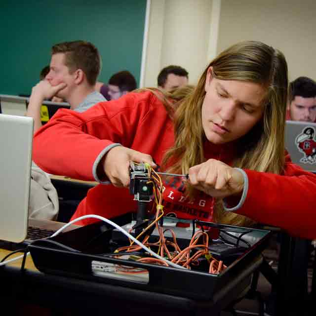 A female student in Engineering class works with a device in class.