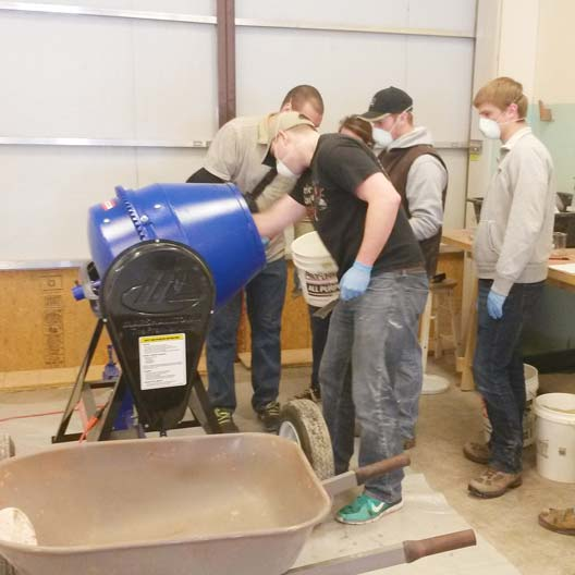 Engineering students mix concrete for a canoe project