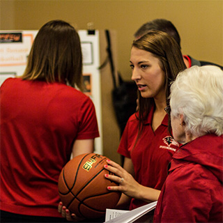 A student holds a basketball during a Discovery Day presentation