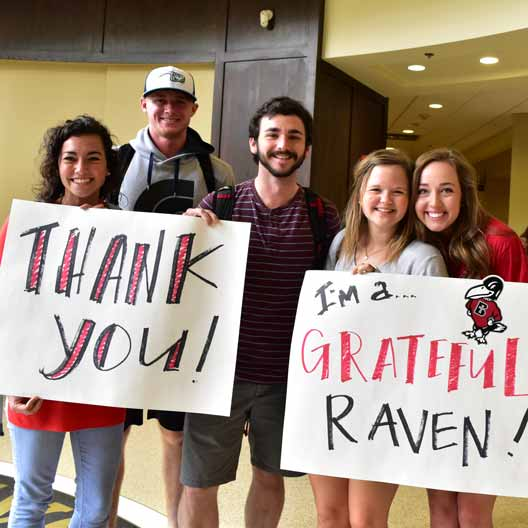 Students holding thank you signs during Grateful Raven Day