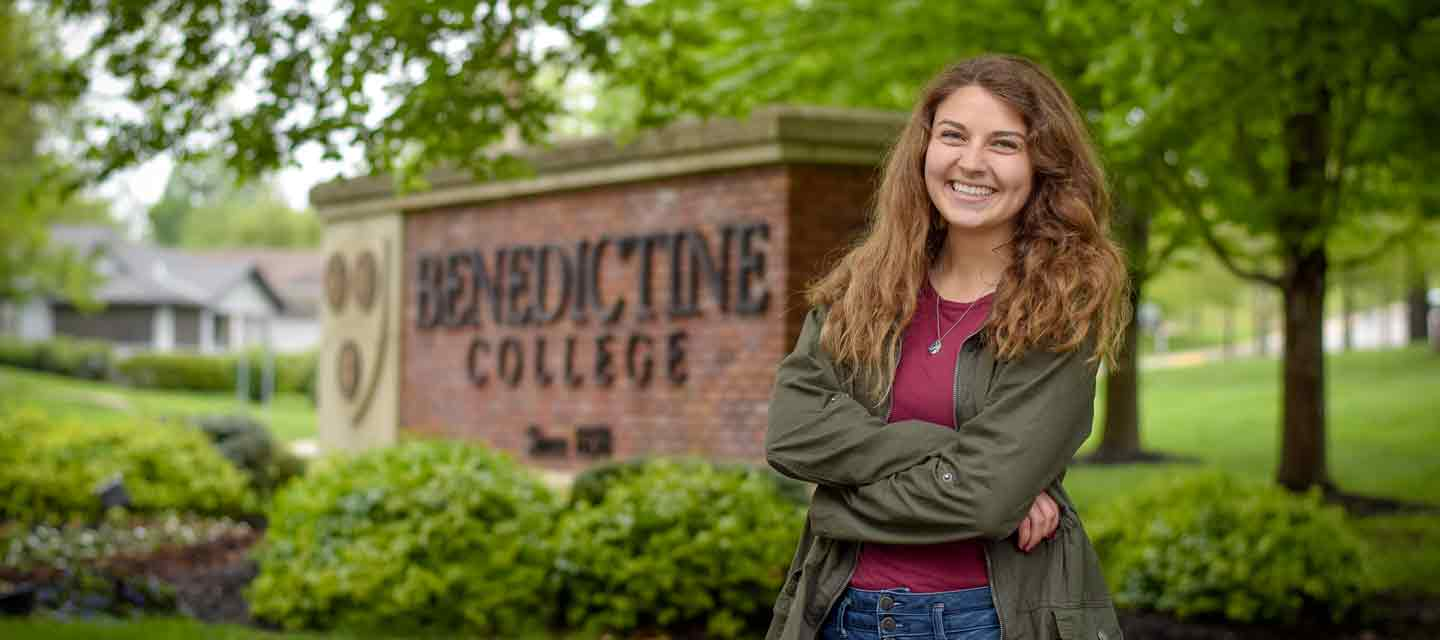 A student poses for a photo near the Benedictine College entrance sign