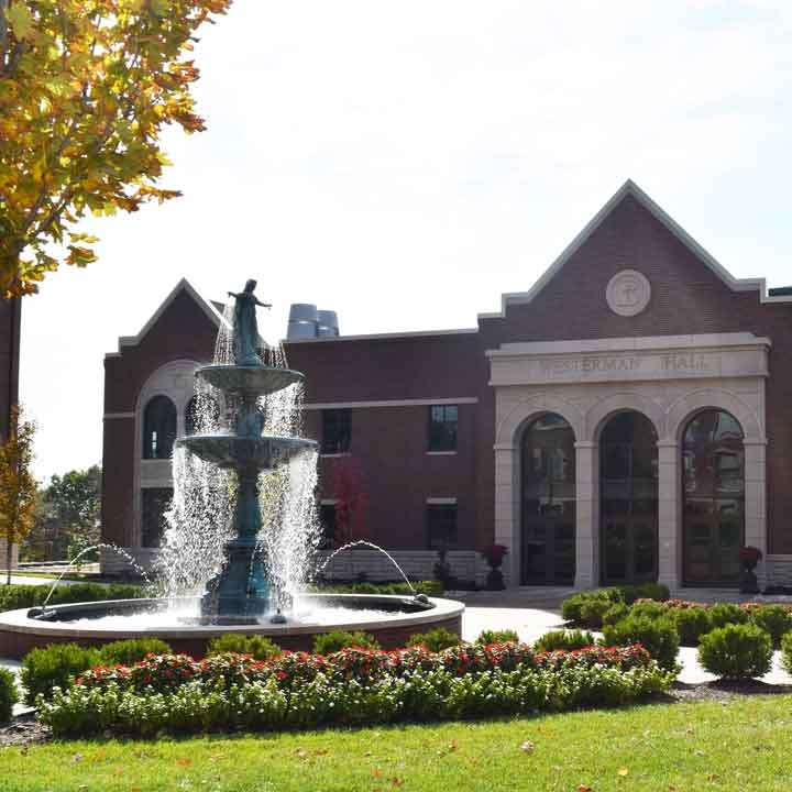 Our Lady of Grace Fountain surrounded by flowers with the Ferrell Academic Center in the background