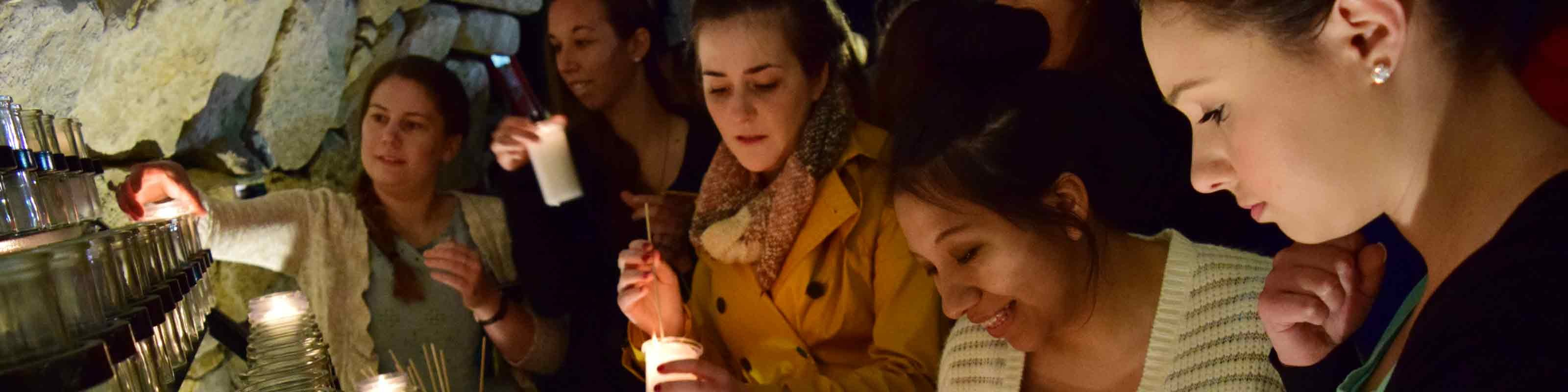 Students light candles at Mary's Grotto